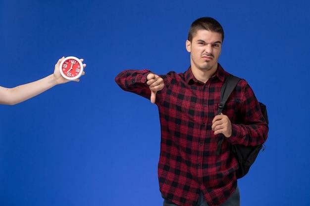 Widok z przodu studenta w czerwonej koszuli w kratkę z plecakiem na niebieskiej ścianie
