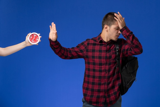 Widok z przodu studenta w czerwonej koszuli w kratkę z plecakiem pozowanie na niebieskiej ścianie