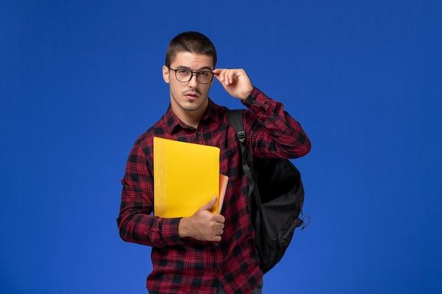 Widok z przodu studenta w czerwonej koszuli w kratkę z plecakiem, trzymając pliki i zeszyt na jasnoniebieskiej ścianie