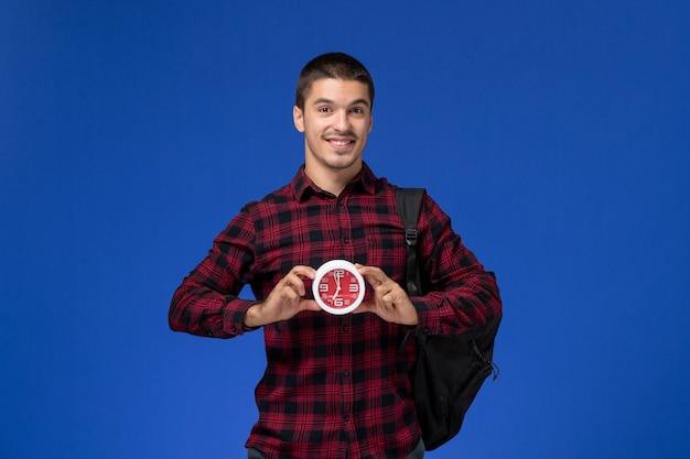 Widok z przodu studenta w czerwonej koszuli w kratkę z plecakiem trzymając zegary uśmiechnięte na niebieskiej ścianie