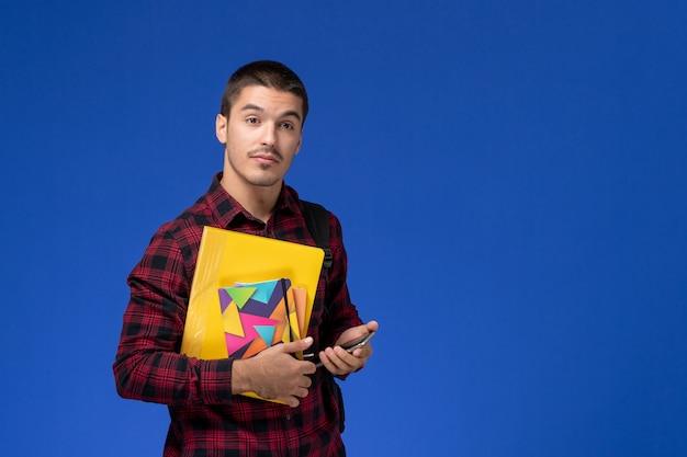 Widok z przodu studenta w czerwonej koszuli w kratkę z plecakiem trzymając zeszyt i pliki z telefonem na niebieskiej ścianie