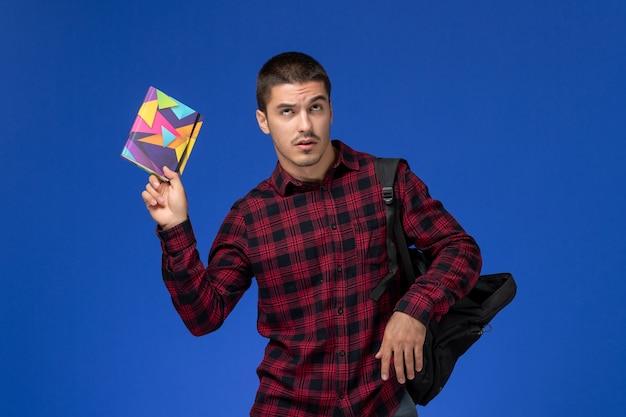 Widok z przodu studenta w czerwonej koszuli w kratkę z plecakiem trzymając zeszyt na niebieskiej ścianie