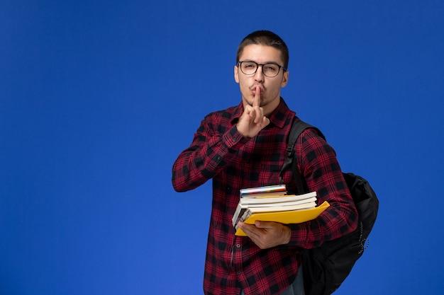 Widok z przodu studenta w czerwonej koszuli w kratkę z plecakiem, trzymając zeszyty na jasnoniebieskiej ścianie