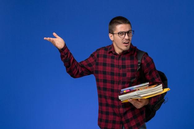 Widok z przodu studenta w czerwonej koszuli w kratkę z plecakiem trzymając zeszyty na niebieskiej ścianie