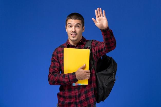 Widok z przodu studenta w czerwonej koszuli w kratkę z plecakiem, trzymając żółte pliki macha na niebieskiej ścianie