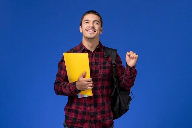Widok z przodu studenta w czerwonej koszuli w kratkę z plecakiem, trzymając żółte pliki radując się na niebieskiej ścianie