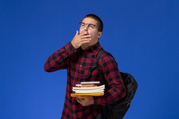 Widok z przodu studenta w czerwonej koszuli w kratkę z plecakiem trzymającym zeszyty ziewający na jasnoniebieskiej ścianie