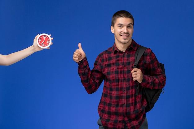 Widok z przodu studenta w czerwonej koszuli w kratkę z plecakiem uśmiechnięty na niebieskiej ścianie