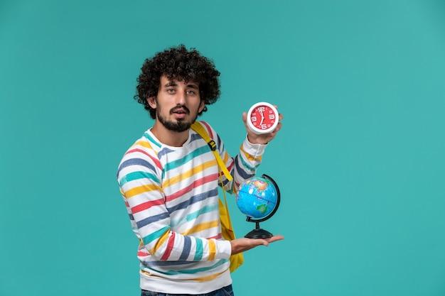 Widok z przodu studenta w pasiastej koszuli na sobie żółty plecak, trzymając okrągły mały glob i zegary na niebieskiej ścianie