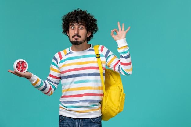 Widok z przodu studenta w pasiastej koszuli na sobie żółty plecak trzymając zegary na niebieskiej ścianie