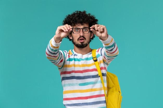 Widok z przodu studenta w pasiastej koszuli na sobie żółty plecak trzymający okulary optyczne na niebieskiej ścianie