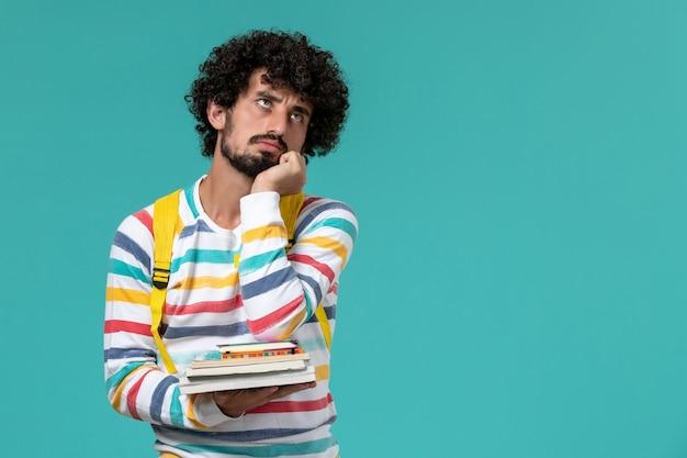 Widok z przodu studenta w paski koszuli na sobie żółty plecak trzymając książki na niebieskiej ścianie