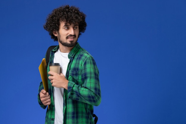 Widok z przodu studenta w zielonej koszuli w kratkę na sobie czarny plecak i trzymając pliki i kawę