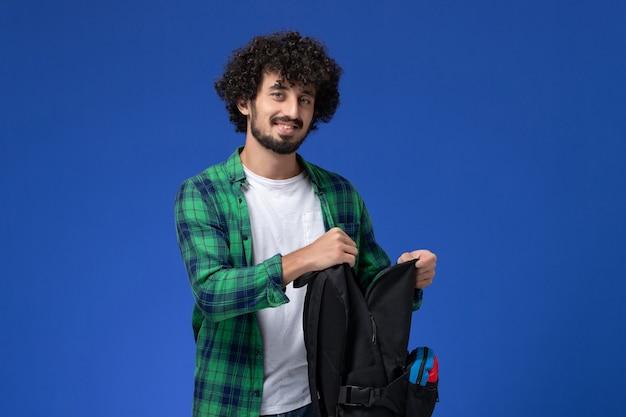 Widok z przodu studenta w zielonej koszuli w kratkę, trzymając czarny plecak na jasnoniebieskiej ścianie