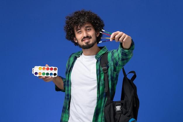 Widok z przodu studenta w zielonej koszuli w kratkę z czarnym plecakiem trzymającym farby do rysowania i frędzle na niebieskiej ścianie