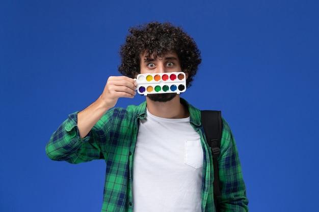 Widok z przodu studenta w zielonej koszuli w kratkę z czarnym plecakiem trzymającym farby do rysowania na niebieskiej ścianie