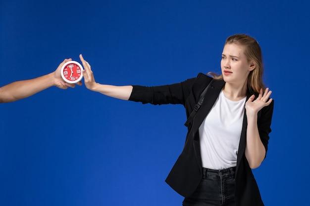 Widok z przodu studentka w czarnej kurtce na sobie plecak boi się zegarów na niebieskiej ścianie szkoła college uniwersytet czas lekcji