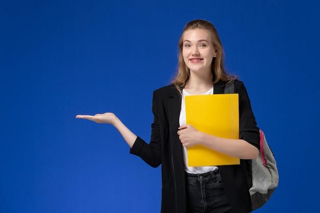 Widok z przodu studentka w czarnej kurtce na sobie plecak i trzymająca żółty plik na lekcjach uniwersytetu na jasnoniebieskiej ścianie