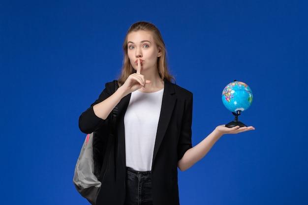 Widok z przodu studentka w czarnej kurtce na sobie plecak trzyma małą kulę ziemską na niebieskim biurku szkoła college uniwersytet ziemia