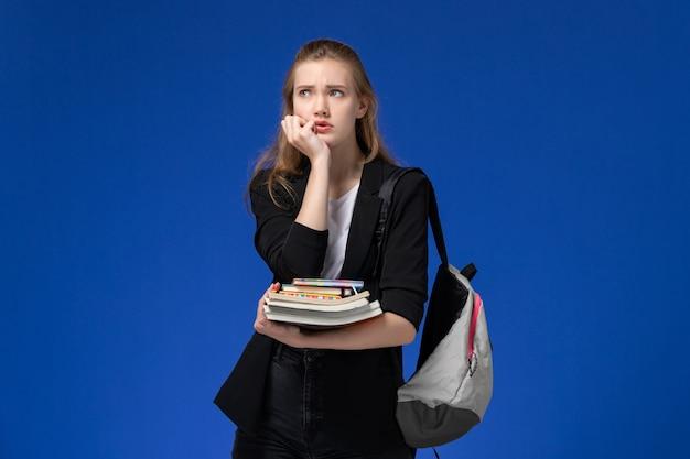 Widok z przodu studentka w czarnej kurtce na sobie plecak, trzymając książki i myśląc na niebieskiej ścianie lekcji kolegium szkoły
