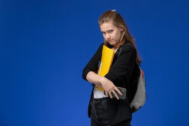 Widok z przodu studentka w czarnej kurtce na sobie plecak, trzymając plik i zeszyt z telefonem na niebieskiej ścianie lekcje uniwersytetu