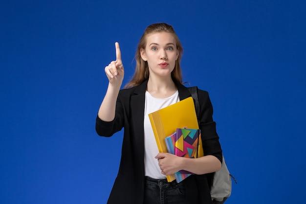 Widok z przodu studentka w czarnej kurtce na sobie plecak trzymając plik z zeszytami na lekcji uniwersytetu na niebieskiej ścianie