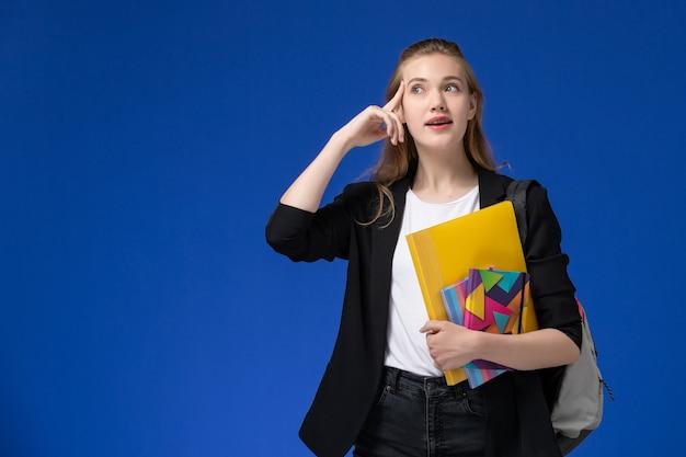 Widok z przodu studentka w czarnej kurtce na sobie plecak trzymając pliki z zeszytami myśli na lekcjach uniwersytetu na niebieskiej ścianie