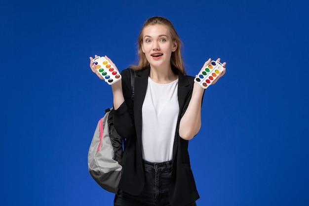 Widok z przodu studentka w czarnej kurtce na sobie plecak trzymający farby do rysowania na niebieskiej ścianie rysunku szkoły artystycznej uczelni