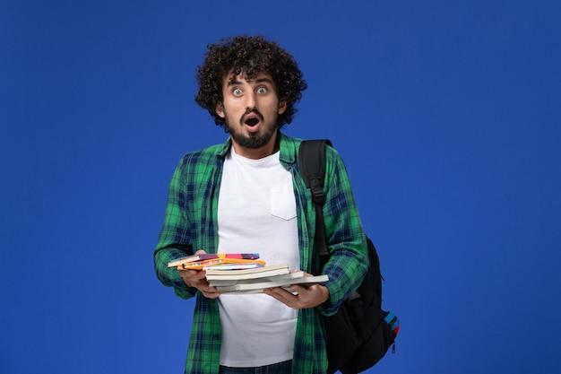 Widok z przodu studentka z czarnym plecakiem, trzymając zeszyty i pliki na niebieskiej ścianie