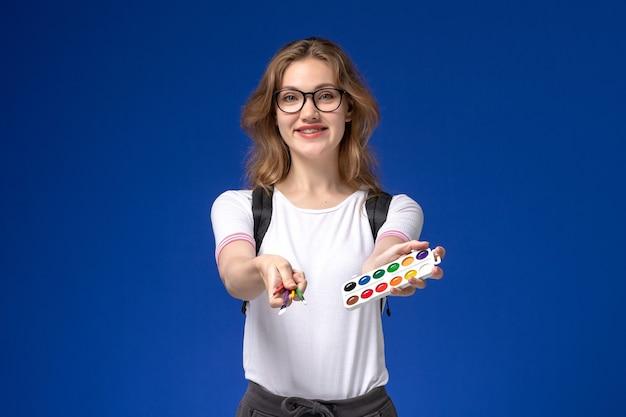 Widok z przodu studentki w białej koszuli na sobie plecak i trzymając pędzle artystyczne na niebieskiej ścianie