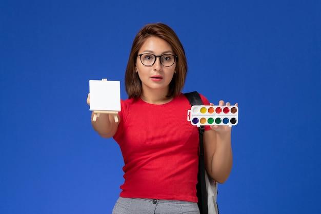 Widok z przodu studentki w czerwonej koszuli z plecakiem trzymającej farby do rysowania na jasnoniebieskiej ścianie