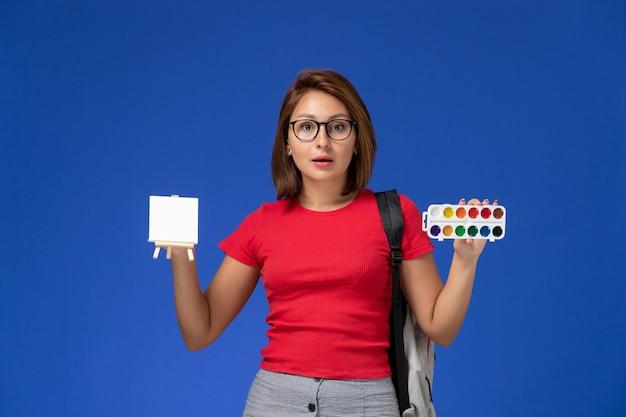 Widok z przodu studentki w czerwonej koszuli z plecakiem trzymającym farby do rysowania na niebieskiej ścianie