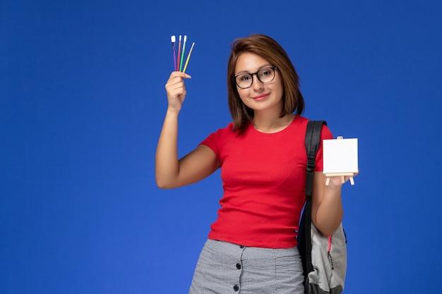 Widok z przodu studentki w czerwonej koszuli z plecakiem trzymającym frędzle do rysowania uśmiechniętej na jasnoniebieskiej ścianie