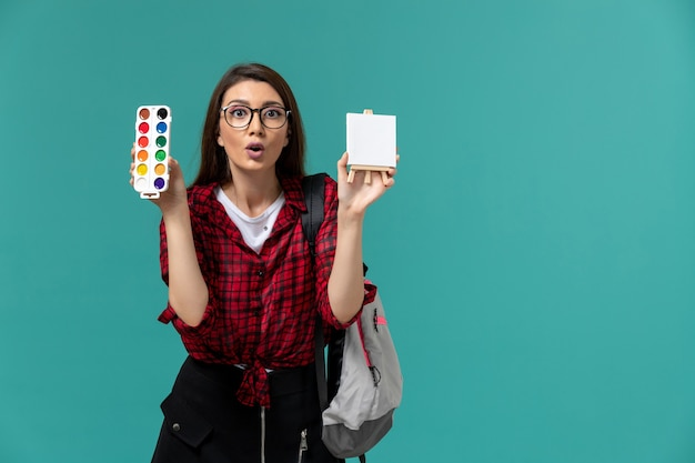 Widok z przodu studentki w plecaku trzymającym sztalugi i farby na jasnoniebieskiej ścianie