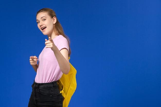 Widok z przodu studentki w różowej koszulce z żółtym plecakiem na jasnoniebieskiej ścianie
