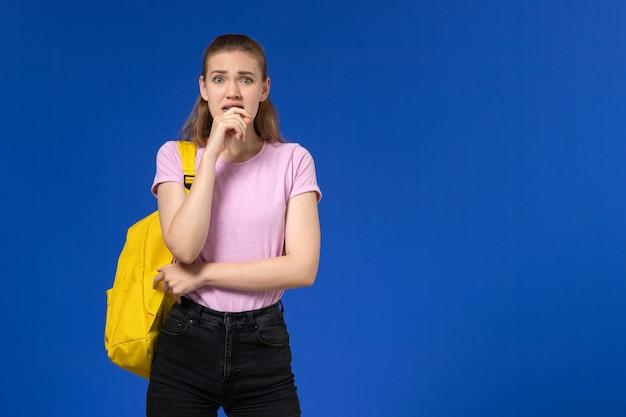 Widok z przodu studentki w różowej koszulce z żółtym plecakiem, przestraszona na jasnoniebieskiej ścianie