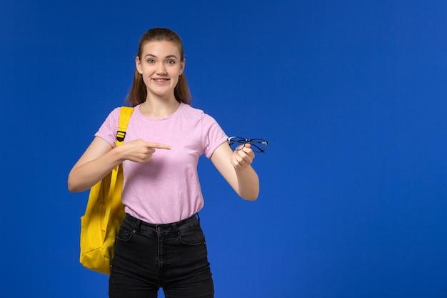 Widok z przodu studentki w różowej koszulce z żółtym plecakiem trzymającej optyczne okulary przeciwsłoneczne na niebieskiej ścianie