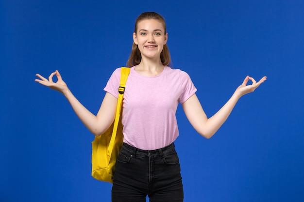 Widok z przodu studentki w różowej koszulce z żółtym plecakiem, uśmiechnięta i pozująca na niebieskiej ścianie