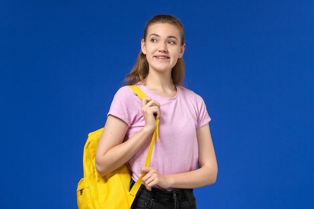 Widok z przodu studentki w różowej koszulce z żółtym plecakiem uśmiechniętym na niebieskiej ścianie