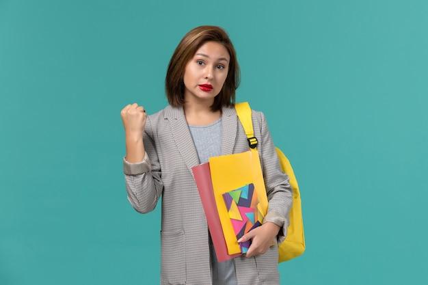 Widok z przodu studentki w szarej kurtce na sobie żółty plecak z plikami i zeszytem na niebieskiej ścianie