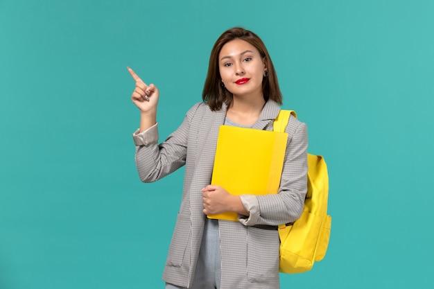 Widok z przodu studentki w szarej kurtce, ubrana w żółty plecak i trzymająca pliki na jasnoniebieskiej ścianie