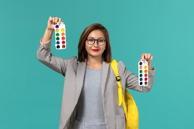 Widok z przodu studentki w szarej kurtce w żółtym plecaku z farbami do rysowania na jasnoniebieskiej ścianie