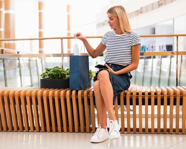 Widok z przodu stylowa kobieta sprawdza torby na zakupy