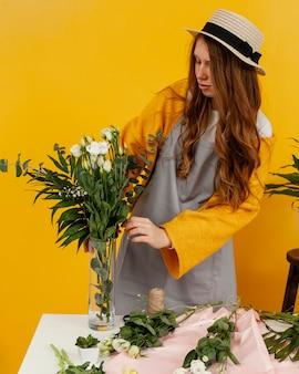 Widok z przodu stylowej kobiety układania kwiatów