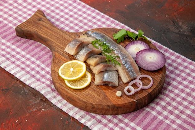 Widok z przodu surowa pokrojona ryba z krążkami cebuli i cytryną na ciemnym naczyniu przekąska posiłek kolor mięso owoce morza
