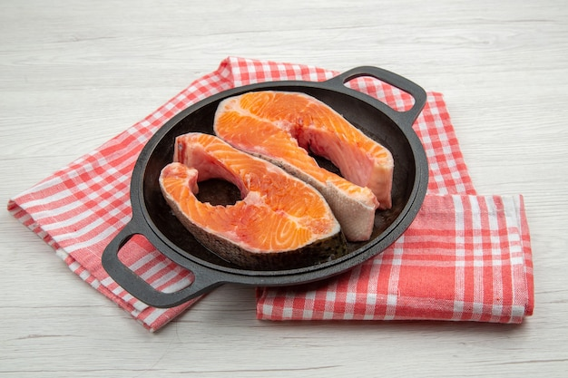 Widok z przodu surowe plastry mięsa wewnątrz czarnej patelni na białym tle żebro jedzenie posiłek zwierzę danie mięso