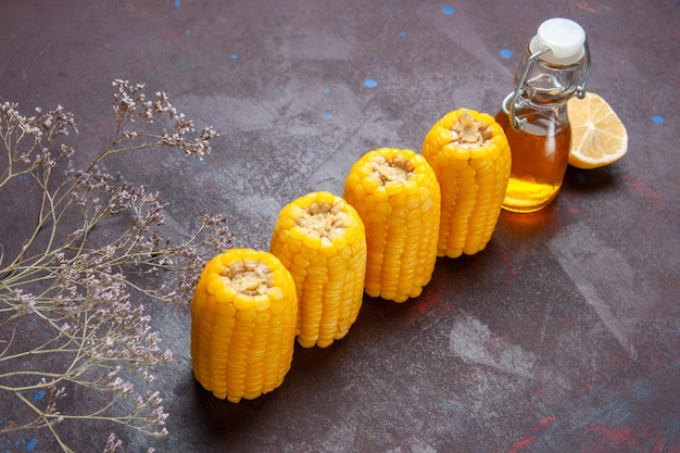Widok z przodu surowe żółte odciski z olejem i cytryną na ciemnej powierzchni przekąska popcornowa roślina kukurydziana