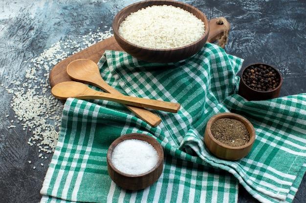 Widok z przodu surowy ryż z przyprawami na ciemnym tle kasze zbożowe kolor zupa jedzenie posiłek nasiona