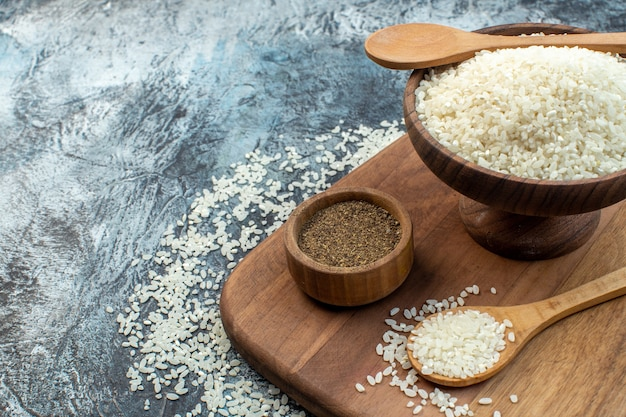 Widok z przodu surowy ryż z przyprawami na ciemnym tle nasiona zboża kolor mączka kasza jedzenie zupa