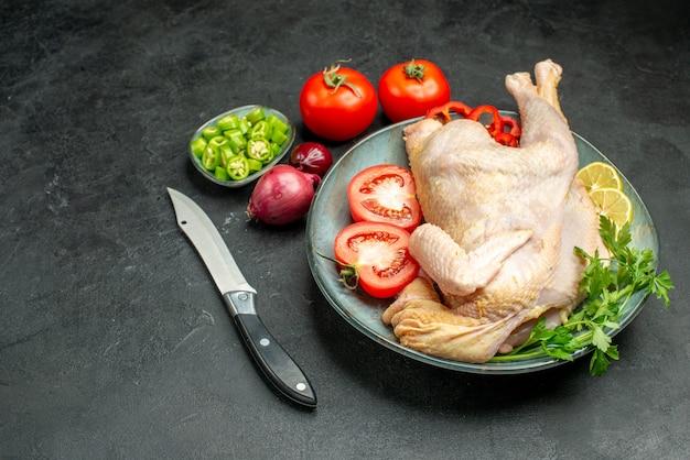 Widok z przodu surowy świeży kurczak wewnątrz talerza z zieleniną i warzywami na ciemnym tle mięso jedzenie kurczak zwierzę